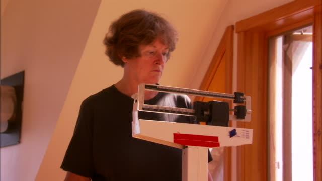 MS Senior woman on weight scale, Halifax, Nova Scotia, Canada