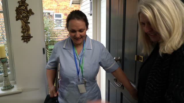senior woman opening front door to nurse - social services stock videos & royalty-free footage