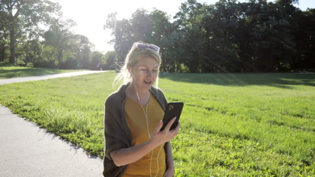senior woman outdoors on spring day in park using phone for video call - slow motion video - springtime stock videos & royalty-free footage