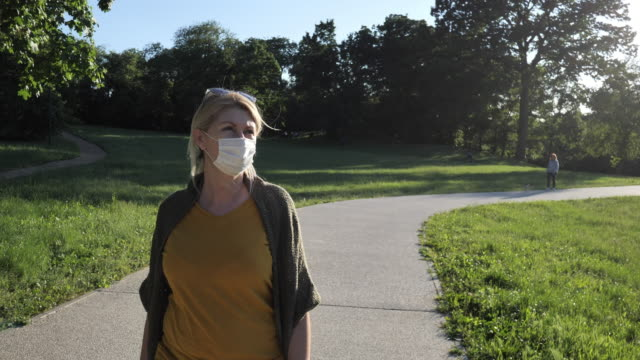 senior woman outdoors on spring day, keeping social distance with face mask on - natural parkland stock videos & royalty-free footage