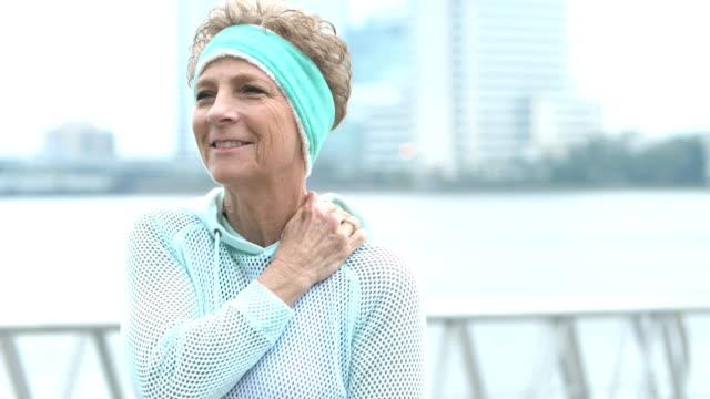 stockvideo's en b-roll-footage met senior vrouw buitenshuis, wrijft pijnlijke schouder, glimlacht - opluchting