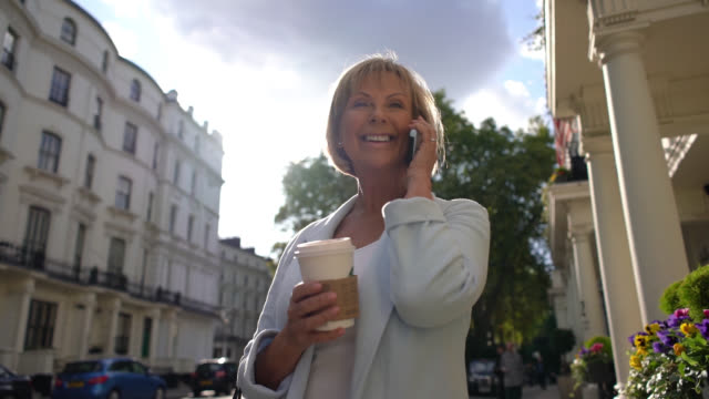 senior woman outside receiving a phonemail while holding a take out coffee on a sunny day - out take stock videos & royalty-free footage