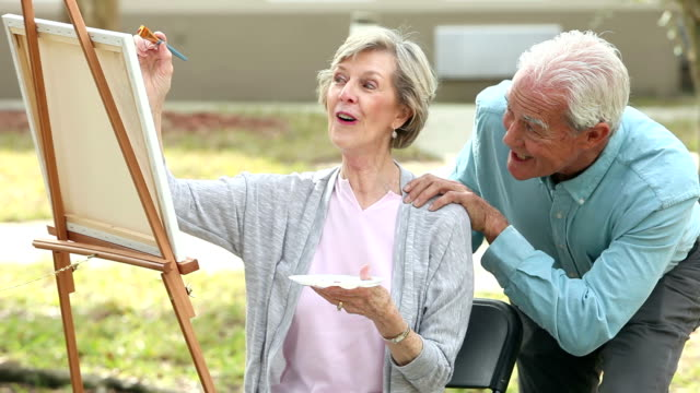 Senior woman painting, husband compliments her work