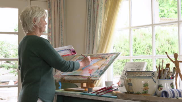 ms rv senior woman painting in her studio - pensionierung stock-videos und b-roll-filmmaterial