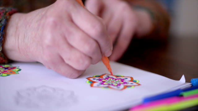 Senior woman paints a coloring book for adults