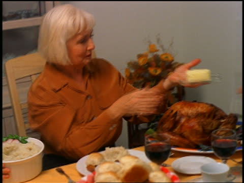 vídeos y material grabado en eventos de stock de pan senior woman passing butter to senior man at holiday table / thanksgiving - mantequera vajilla
