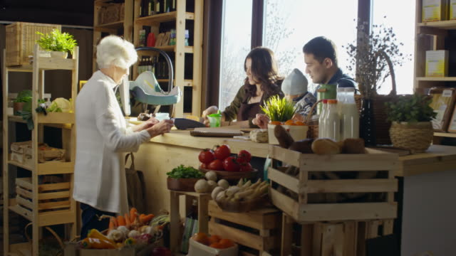 senior woman paying for vegetables at farm shop - part of a series stock videos & royalty-free footage