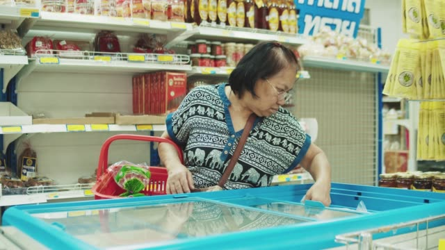 Senior woman pick up products from refrigerator