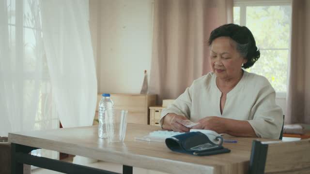 vídeos y material grabado en eventos de stock de la mujer de la tercera edad recogiendo medicamentos de la bolsa de medicamentos en una caja organizadora de píldoras diaria en casa. - organizador personal