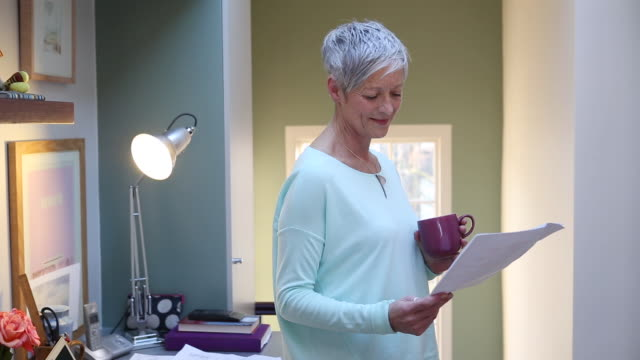 senior woman picks up paperwork from desk reads it while turning and sips from cup of tea