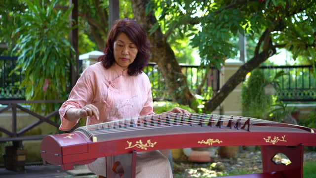 vídeos de stock e filmes b-roll de senior woman playing chinese instrument guzheng - arte, cultura e espetáculo