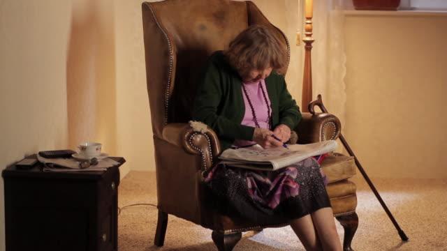 ms tu td senior woman playing crossword puzzle in newspaper  / berlin, germany - crossword stock videos & royalty-free footage