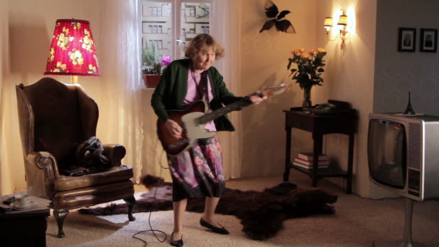 ws senior woman playing electric guitar / berlin, germany - television show stock-videos und b-roll-filmmaterial