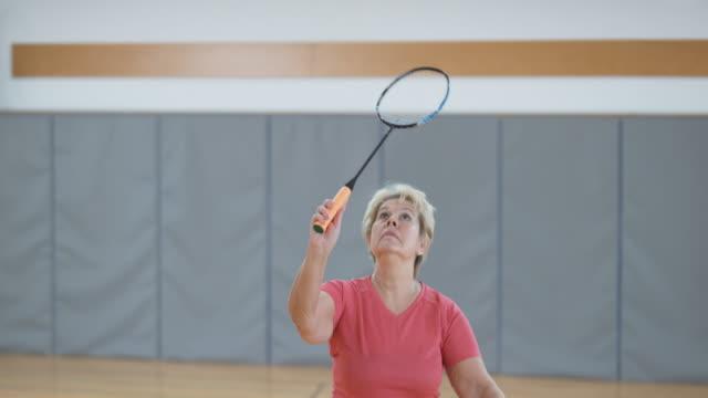 Senior woman playing indoor badminton