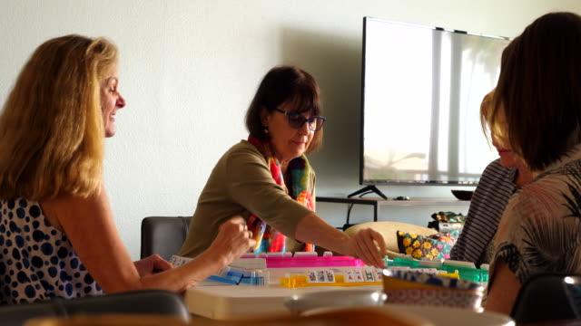 ms senior woman playing mahjong in living room with friends - 余暇 ゲームナイト点の映像素材/bロール
