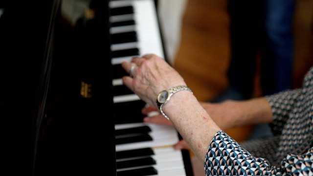 senior woman playing piano for guest - piano stock videos & royalty-free footage
