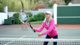 Senior woman playing tennis in tennis court 4k