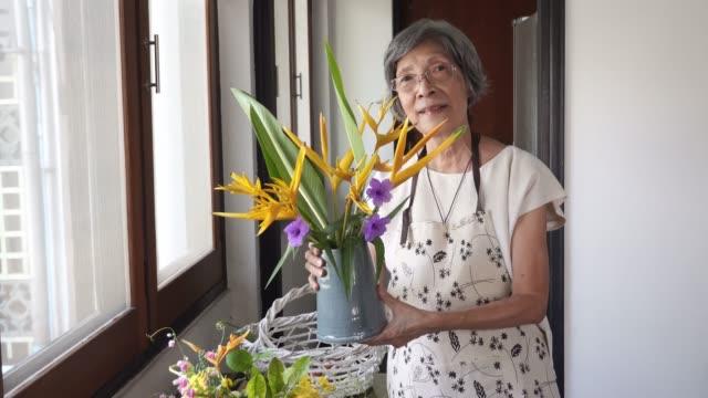 senior woman portrait doing flower arrangement - flower arrangement stock videos & royalty-free footage