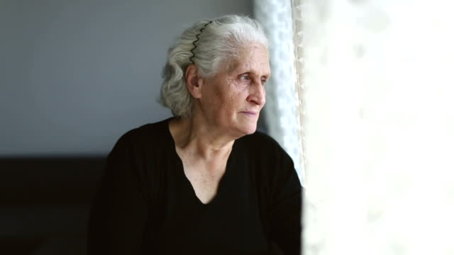 senior woman portrait looking at camera and then through window behind the curtain - the ageing process stock videos & royalty-free footage