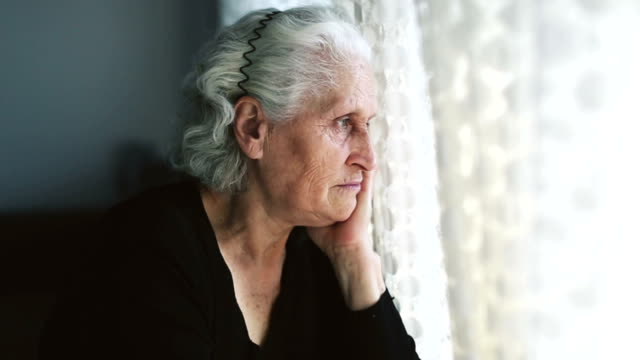 dolly: senior woman portrait looking through window behind the curtain - terza età video stock e b–roll