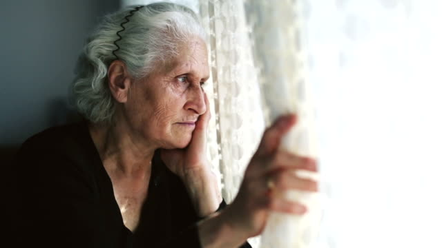 dolly: senior woman portrait looking through window behind the curtain - the ageing process stock videos & royalty-free footage