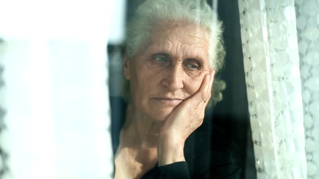 senior woman portrait looking through window behind the curtain - turkey middle east stock videos & royalty-free footage