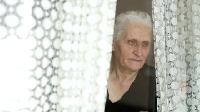 vídeos y material grabado en eventos de stock de retrato de mujer senior mirando a través de la ventana detrás de la cortina - parpadear