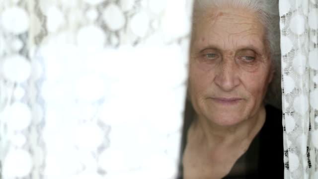 vídeos de stock, filmes e b-roll de retrato de mulher sênior, olhando pela janela atrás da cortina - cabelo branco
