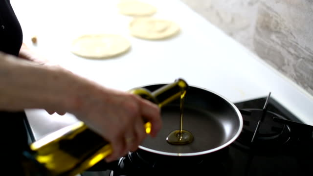 senior woman pouring cooking oil into frying pan before cooking delicious flatbread in the kitchen - olive oil stock videos & royalty-free footage