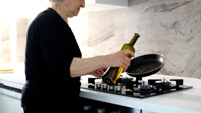 Senior woman pouring cooking oil into frying pan before cooking delicious flatbread in the kitchen