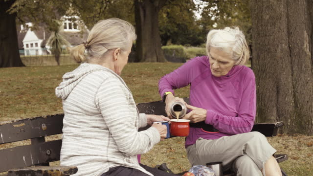 Senior woman pours hot drink from flask, friend is holding mugs, sitting in park.