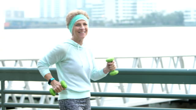 senior woman power walking with hand weights by water - racewalking stock videos and b-roll footage