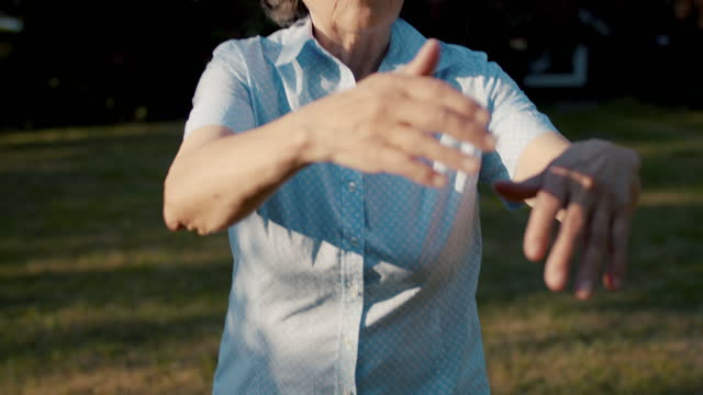 senior woman practicing qigong in garden of her house - zen like stock videos & royalty-free footage