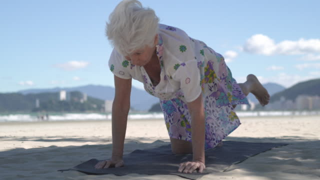 vídeos de stock, filmes e b-roll de senior woman practicing yoga on the beach - ajoelhando se