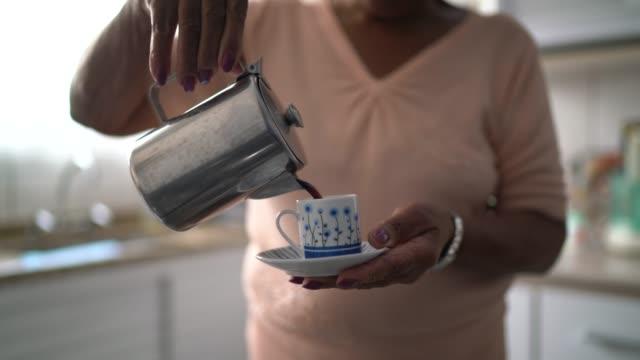 vídeos de stock, filmes e b-roll de idosa prepara café de manhã em casa - xícara de café