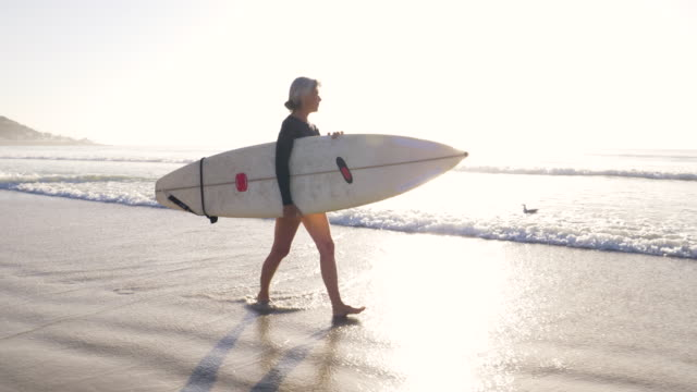 senior woman preparing to go surfing at sunrise - pensionierung stock-videos und b-roll-filmmaterial