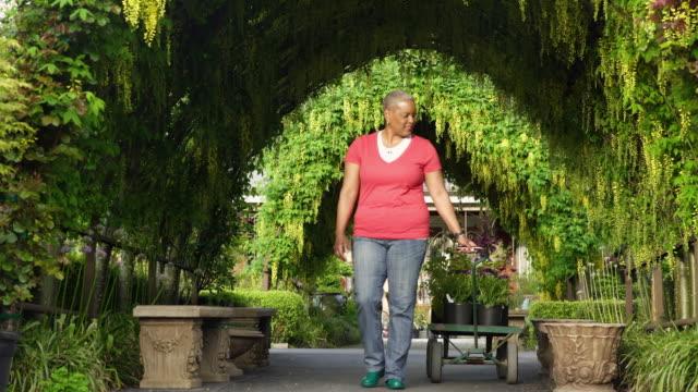 Senior woman pulling a cart in a garden