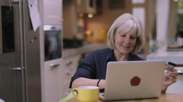 Senior woman purchasing online using laptop