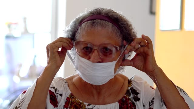 senior woman putting a protective mask on her face - senior adult stock videos & royalty-free footage
