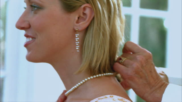 cu senior woman putting necklace on bride / tampa, florida, usa - necklace stock videos & royalty-free footage