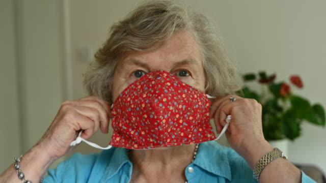 vídeos de stock, filmes e b-roll de idosa colocando máscara facial caseira durante pandemia covid-19 - home made