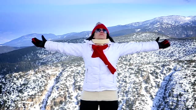Senior woman raises her hands and enjoys a beautiful winter landscape at the top of the mountain