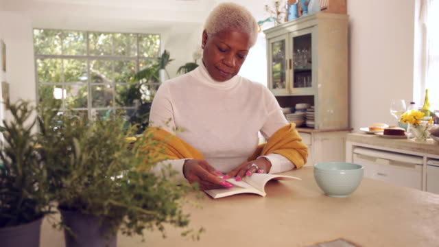 senior woman reading a book in her kitchen - book club stock videos & royalty-free footage