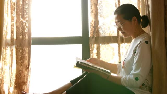 ウィンドウによって本を読む年配の女性 - 屋内点の映像素材/bロール