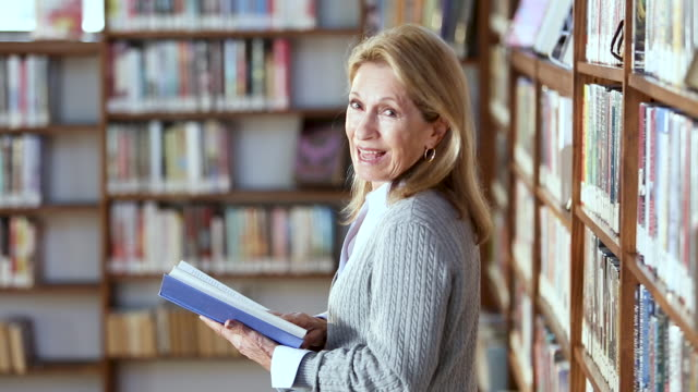 senior woman reading book in library - librarian stock videos & royalty-free footage