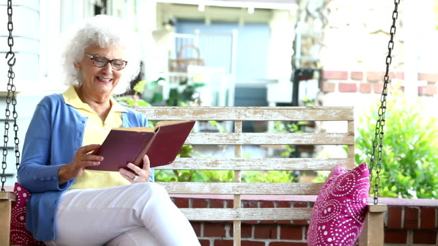 Senior woman reading book on porch swing