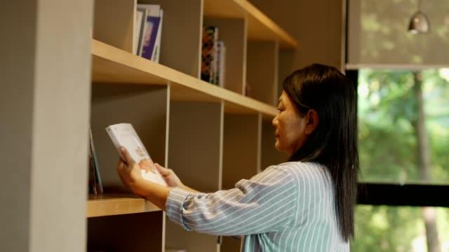 senior woman reading book - librarian stock videos & royalty-free footage