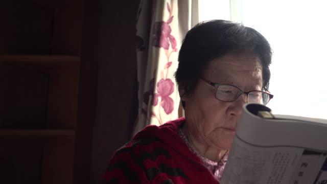vídeos de stock, filmes e b-roll de a senior woman reading book - óculos de leitura