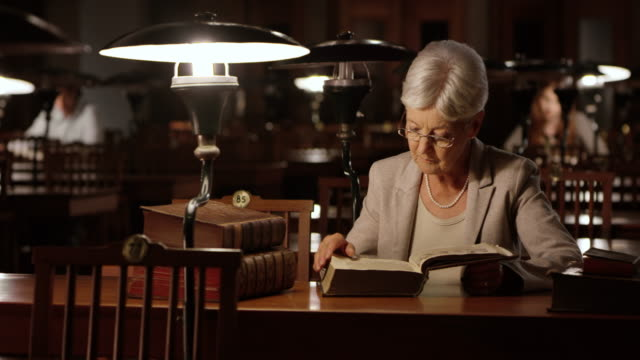ds senior woman reading in library at night - library stock videos and b-roll footage