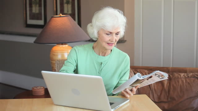 ms senior woman reading magazine and using laptop at home, eastville, virginia, usa - eastville stock videos and b-roll footage